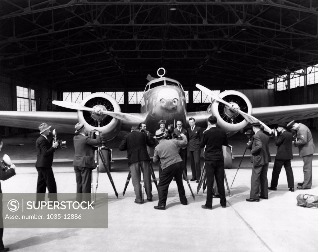Stock Photo: 1035-12886 United States:  1937 Photographers taking photos of (L-R), Paul Mantz, Amelia Earhart, Harry Manning, and Fred Noonan, all posed in front of Earhart's Lockheed Electra 10E