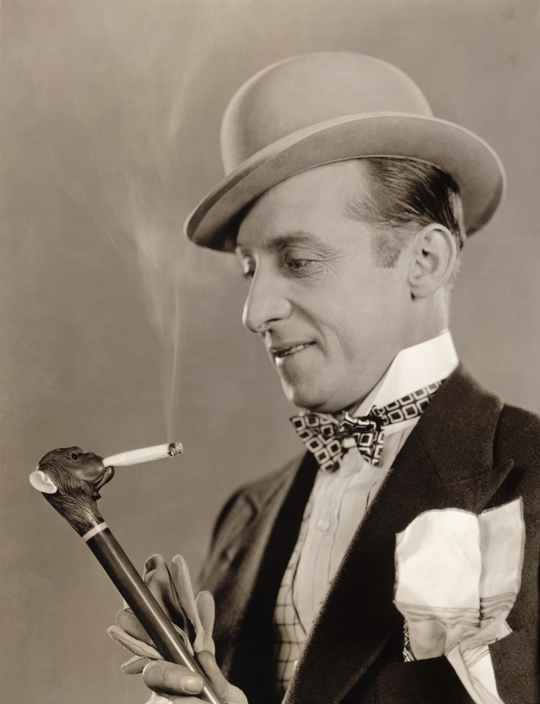 Stock Photo: 1035-1105 Close-up of a mature man holding a cane with a cigarette