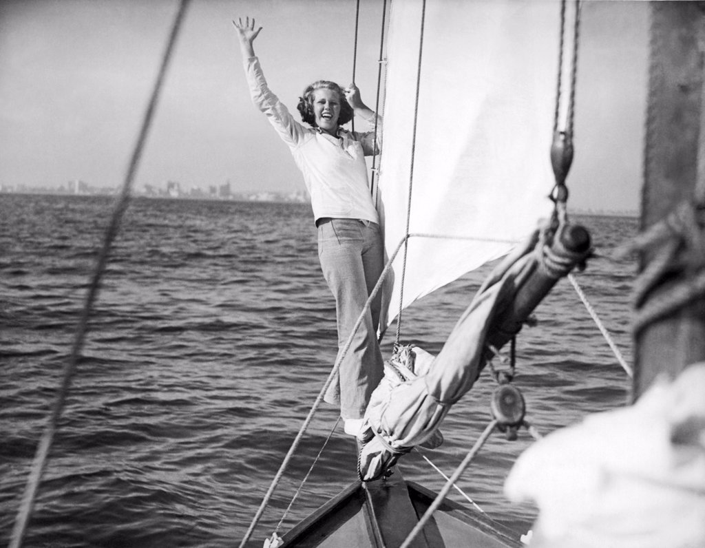 Stock Photo: 1035-11430 Long Beach, California:  c. 1936. A woman on the bow sprit signals that the jib is closehauled and set for the beat back to shore.©Underwood Archives
