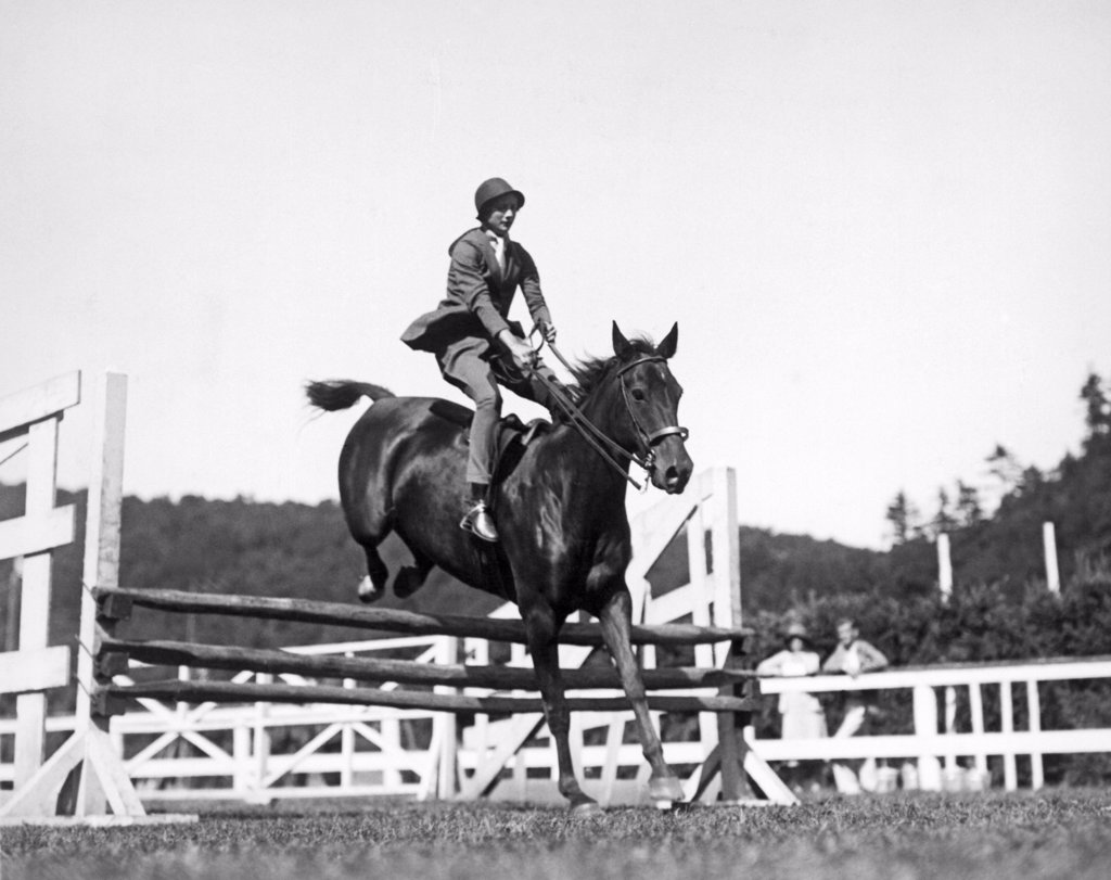 Tuxedo Park, New York:  c. 1929. New York Social Blue Book member Miss Edith Betts going over the jumps in the Tuxedo Junior Horse Show for the benefit of Tuxedo Memorial; Hospital. : Stock Photo