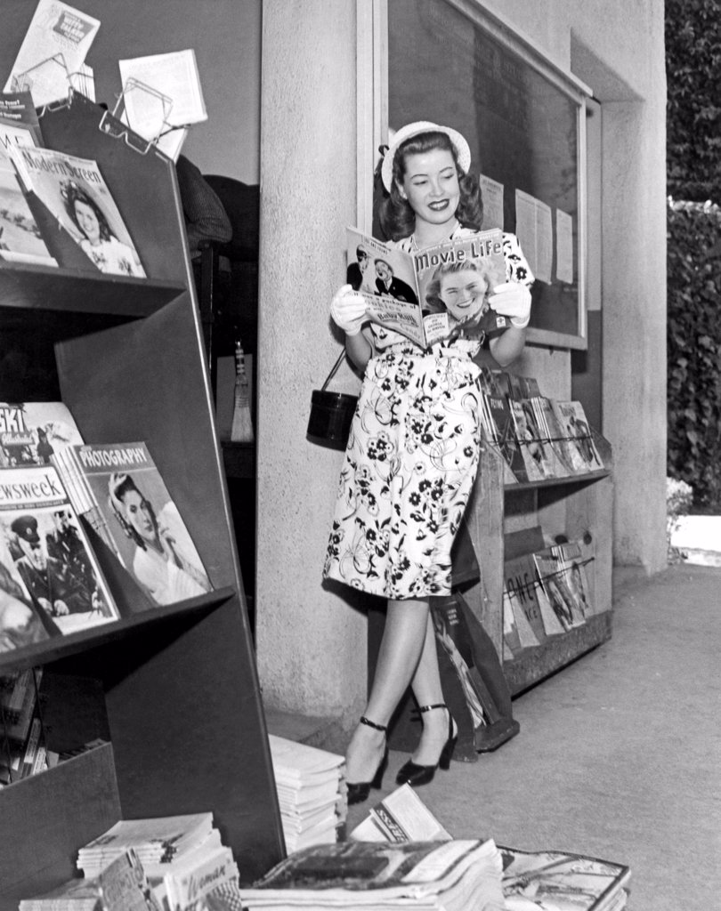 Stock Photo: 1035-11607 Hollywood, California:   April, 1945. A stylish young woman wearing a white hat and  gloves peruses the latest edition of 'Movie Life' at a magazine stand.