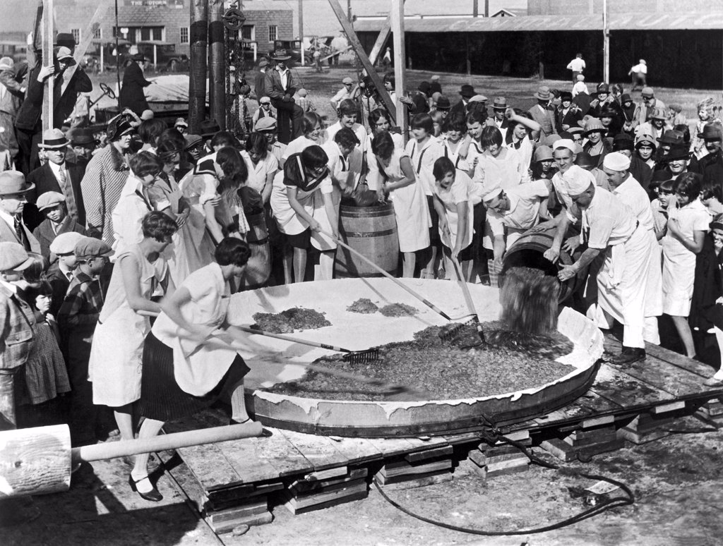 Stock Photo: 1035-11659 Yakima, Washington:   October, 1927. Bakers loading the 400 gallons of apples used to make the world's largest apple pie to celebrate National Apple Week in Yakima. The pie is 10 feet across, and it took five cords of wood to heat the oven to bake it. It weighs 1 ton, and was consumed by 2000 school children.