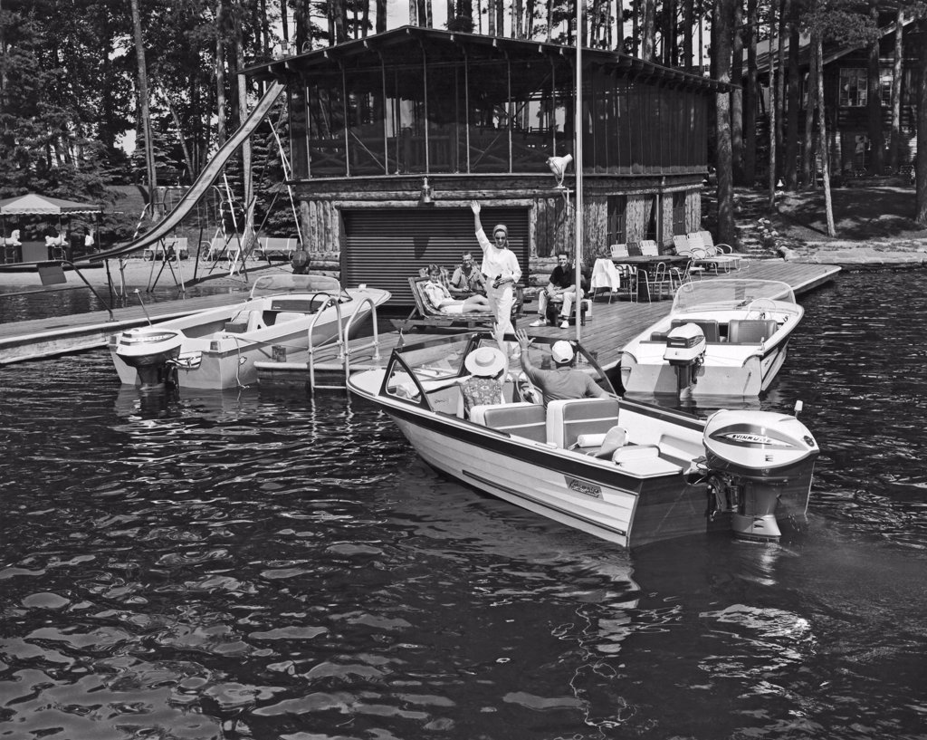 Stock Photo: 1035-11676 United States:  c. 1960. A couple arrives by motor boat to join others on the deck.
