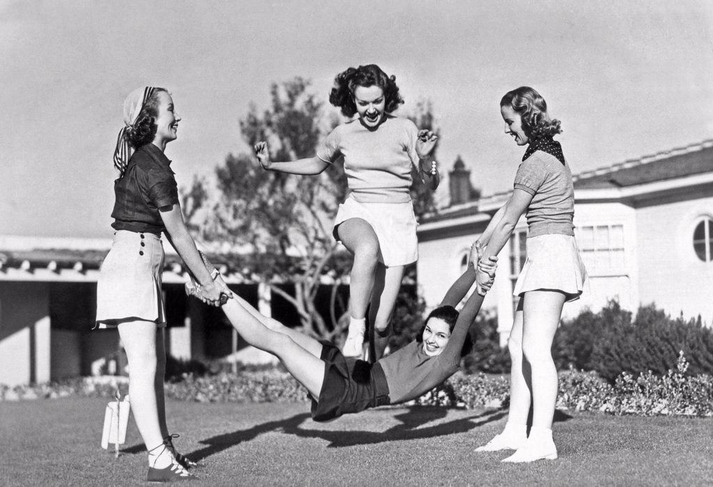 Hollywood, California:  1938. Margaret Randall and Marion Weldon swing Paula De Cardo as a human jump rope for Gwen Kenyon to celebrate the completion of the Paramount picture, 'College Swing'. : Stock Photo