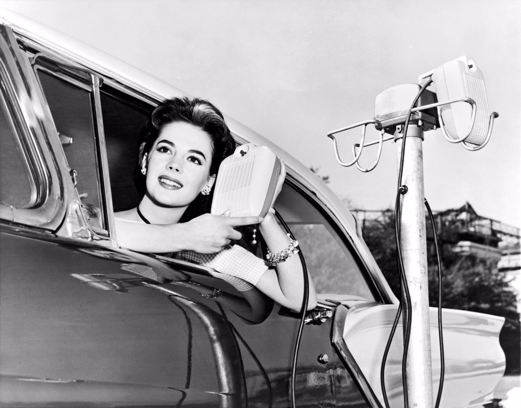 Stock Photo: 1035-11813 Hollywood, California: 1957. Natalie Wood displays the new drive in-movie speakers as she leans out of her car window.
