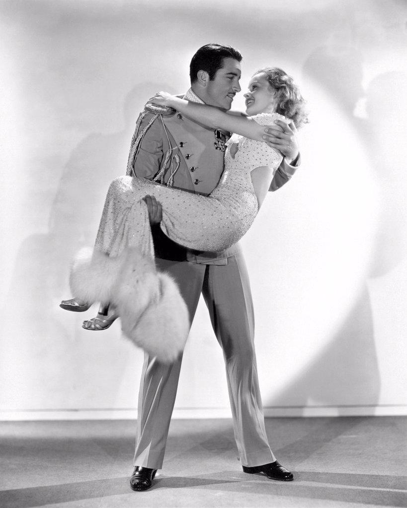 Hollywood, California:  1933. John Boles gives lovely Lilian Harvey a lift in the film, 'My Lips Betray'. : Stock Photo