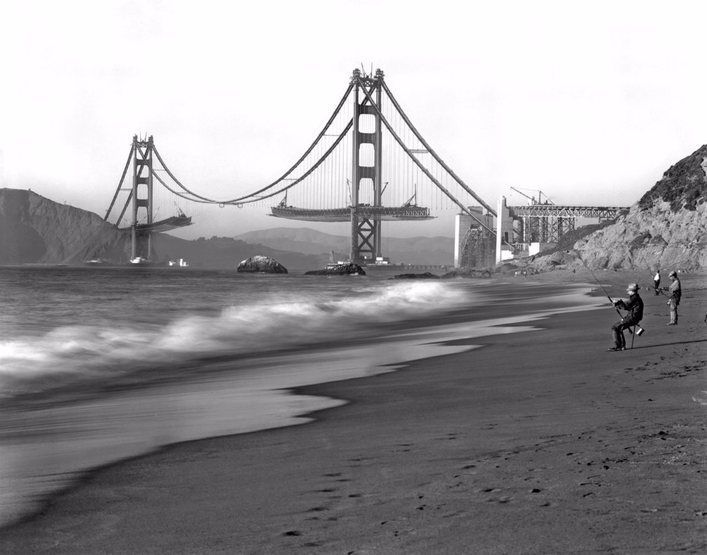 San Francisco, California:   c.1936. Fishermen on Baker Beach enjoy the view of the Golden Gate Bridge under construction. : Stock Photo