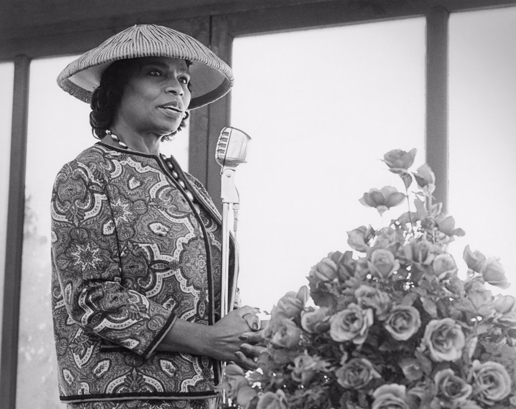 United States:  c. 1940. Marian Anderson wearing a hat speaking at a microphone. : Stock Photo