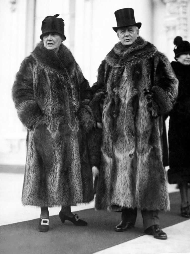 Stock Photo: 1035-12007 Washington, D.C.:  January 2, 1928. Postmaster General and Mrs. Harry New leaving the White House after the New Year reception today. Their coon skin coats of collegiate fame attracted considerable attention among the more somber formal wear of the other Cabinet members.