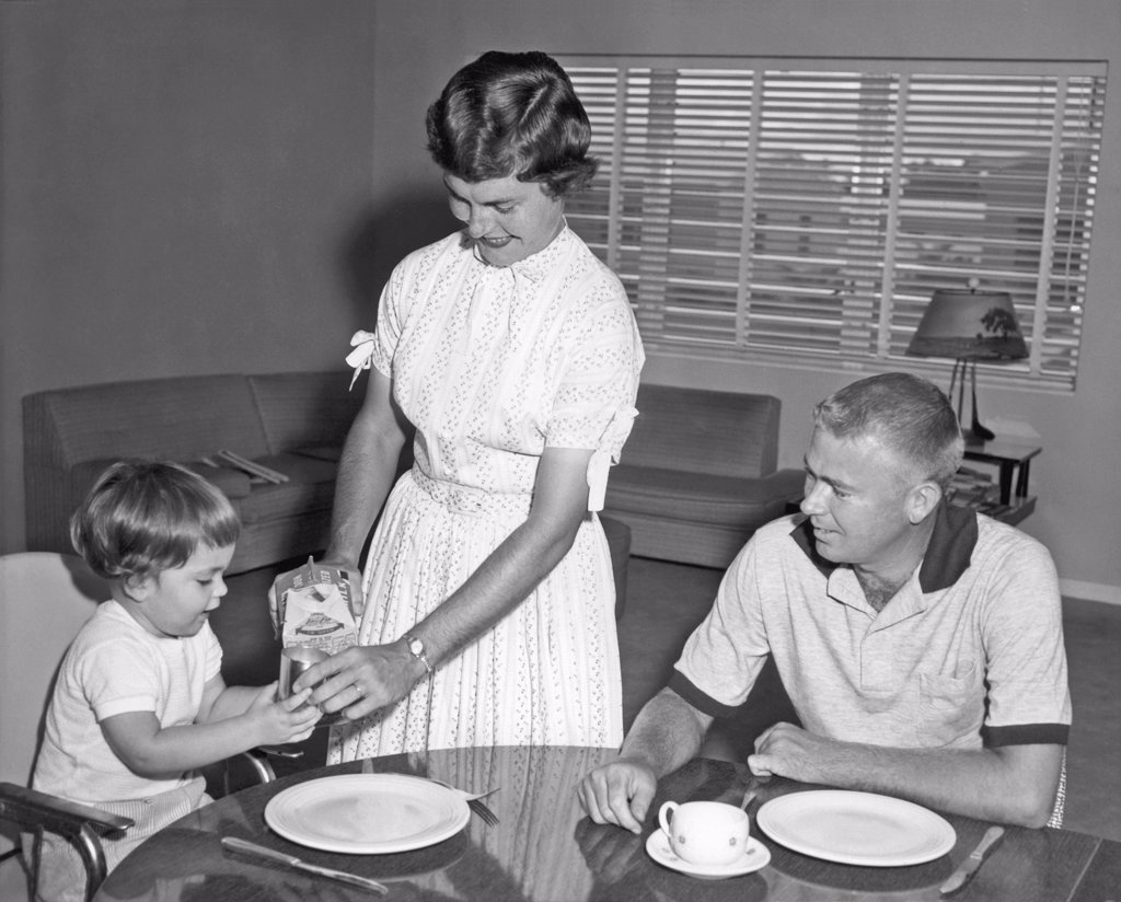 Stock Photo: 1035-12009 United States:  c. 1955. A mother pours a glass of milk for a young child at the kitchen table while the father looks on.