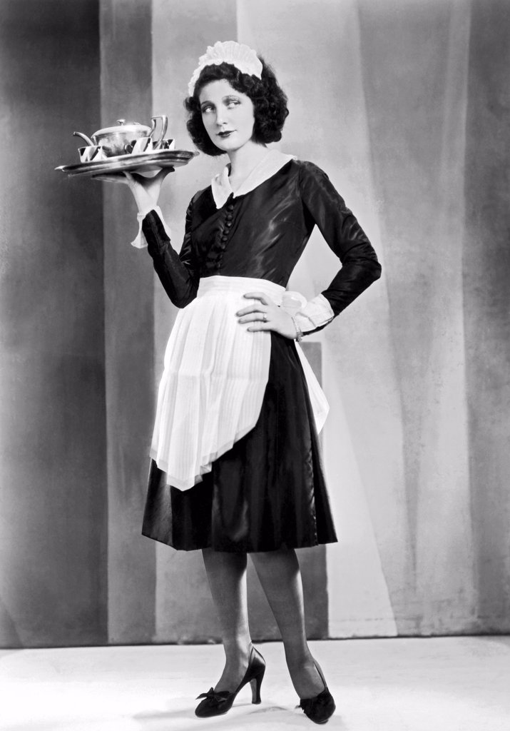 Hollywood, California:  c. 1920. A waitress with a serving tray, possibly in a silent movie. : Stock Photo