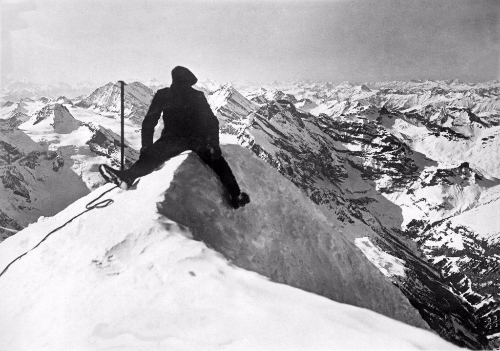 Stock Photo: 1035-12067 Switzerland:  c. 1928. A successful mountain climber sits on top of the world, the famous Jungfrau in the Bernese Oberland in Switzerland