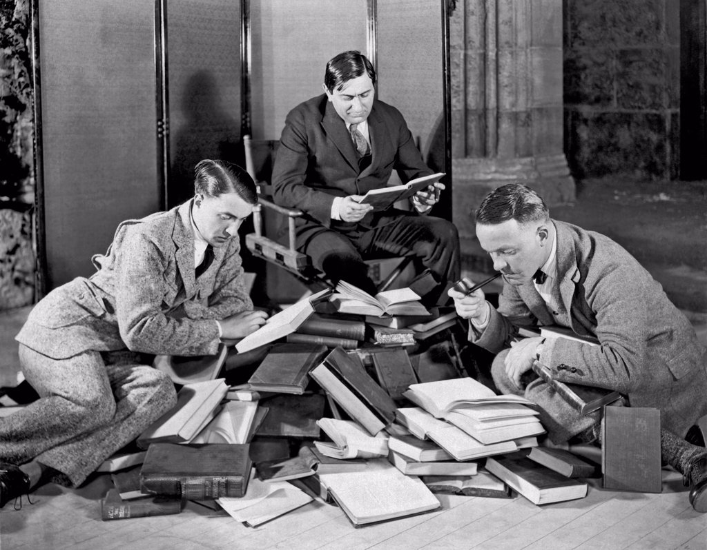 Hollywood, California:  c. 1927. Ernst Lubitsch (1898-1947) at the center with two other men searching through a large pile of books. : Stock Photo