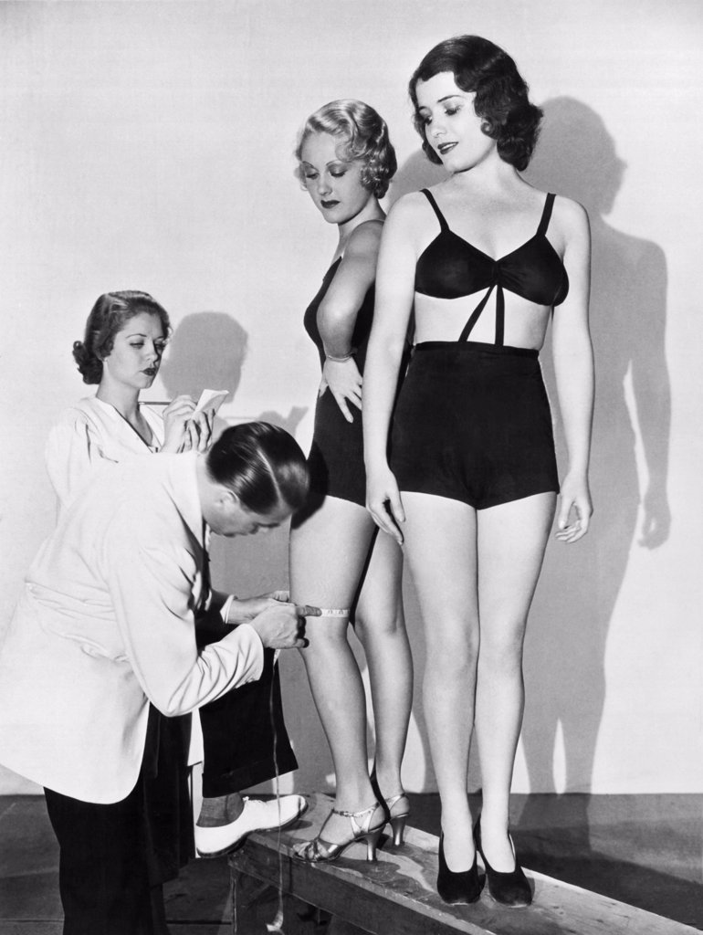 Hollywood, California:  July 24, 1933. A Paramount director measuring a girl's leg for film role. LeRoy Prinz, the dance director for Paramount insists upon certain measurements for roles in the chorus line in 'Too Much Harmony'. Audrene Brier and Virginia George both have the rigth size legs - 14 inches just above the knee. : Stock Photo