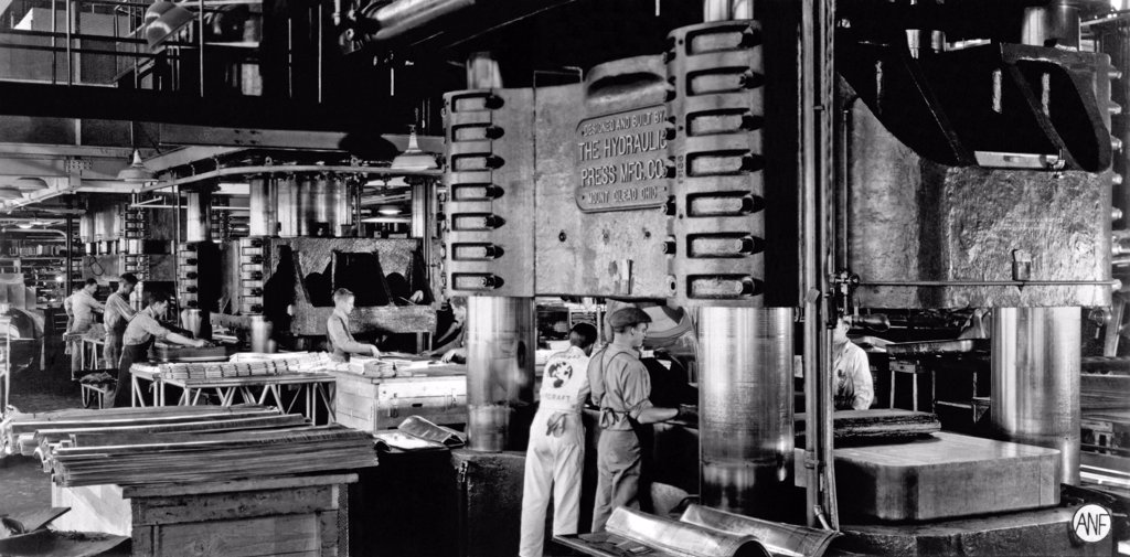 Stock Photo: 1035-12135 Santa Monica, California:  c. 1942. A Douglas Aircraft plant using extremely hard rubber as part of the dies to cut and form aluminum parts for airplanes for the World War II production effort. The rubber is compressed to the hardness of steel, and using the Guerin process, is forced into the dies to create the sheetmetal parts.