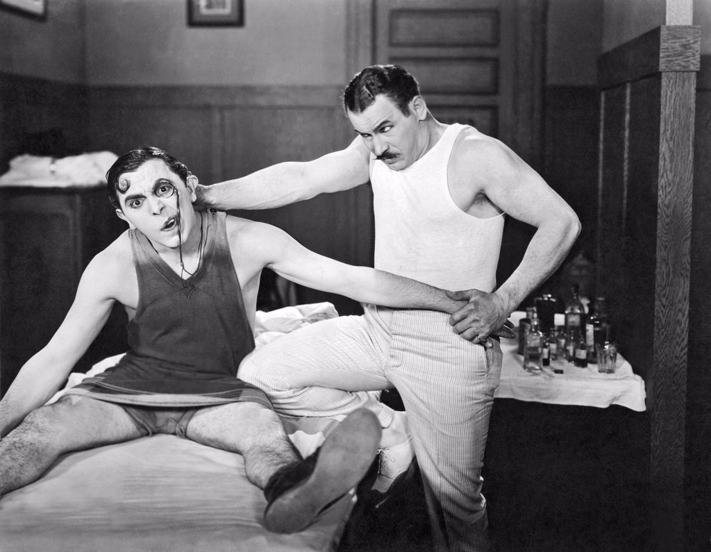 Stock Photo: 1035-12142 Hollywood, California: 1925. Lupino Lane gets some dedicated bodywork done by his trainer  in the film, 'The Fighting Dude'.