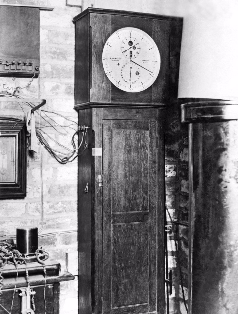 Stock Photo: 1035-12159 Greenwich, England:   August 20, 1924. The clock of the world, the famous chronometer at the Royal Observatory in Greenwich, England, the starting point of longitude on the world's maps. The Royal Astronomer has announced that time signals from this clock are now to broadcast 'by ether'  by the British Broadcasting Company so that every radio fan can keep his watch accurate.
