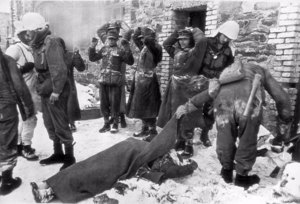 Stock Photo: 1035-12238 Germany:   February 14, 1945. An American soldier lifts the blanket from a fellow soldier to see if he was a friend, while captured German soldiers stand with their hands on their heads in this scene from somewhere on the U.S. First Army front.