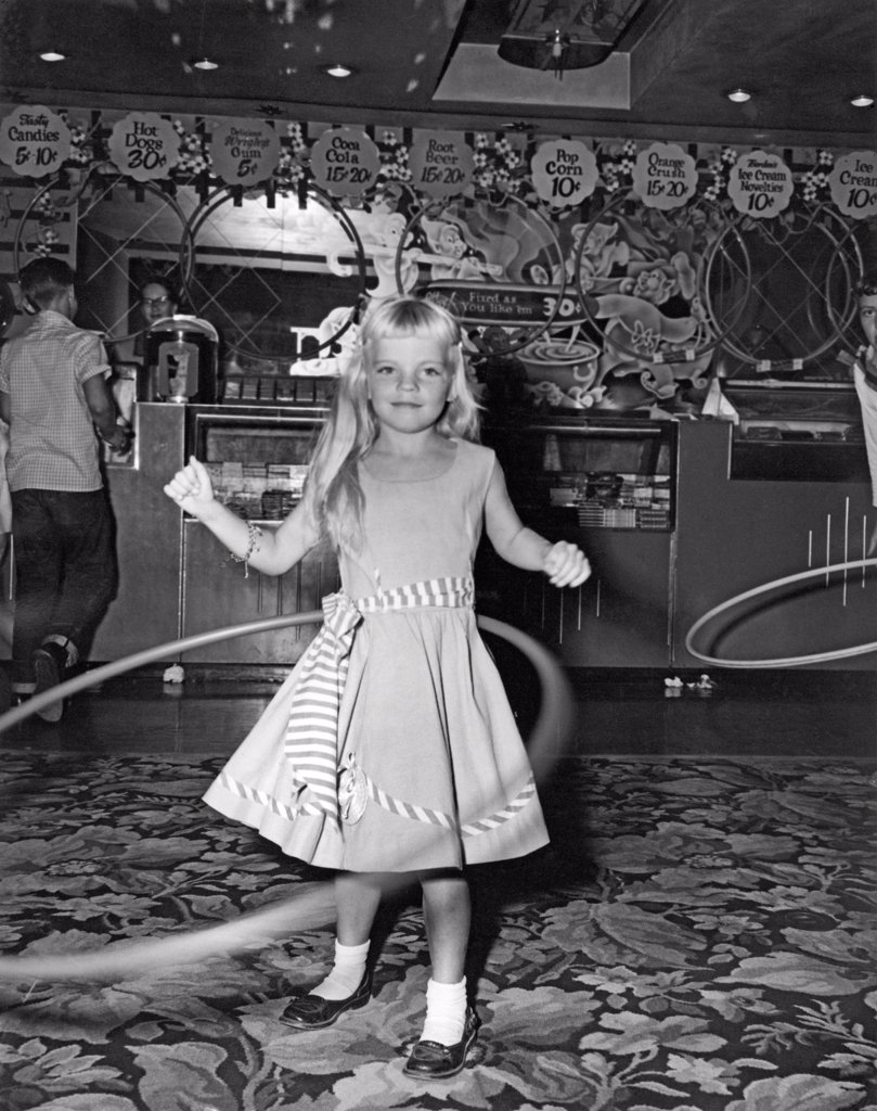 Stock Photo: 1035-12313 United States:  1958. The hula hoop craze sweeps the country. Over 100 million were sold in the United States in the first year. This contest was held in a movie theater lobby, back when popcorn cost a dime and only came in one size.