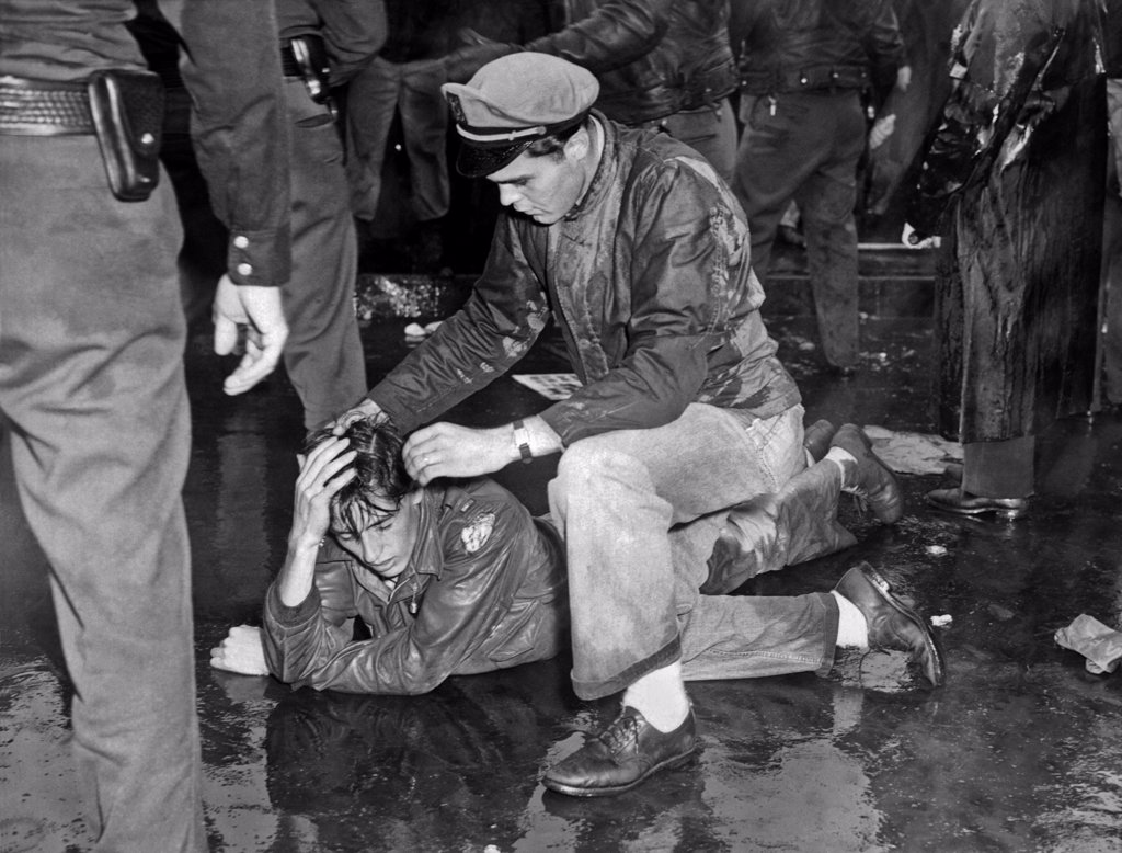 Los Angeles, California: October 1, 1946. An injured demonstrator at the MGM Studios lies on the pavement as a comrade tries to aid him after the battle with the police and deputy sheriffs. Many of the paraders are war veterans who have been locked out during the strike. : Stock Photo