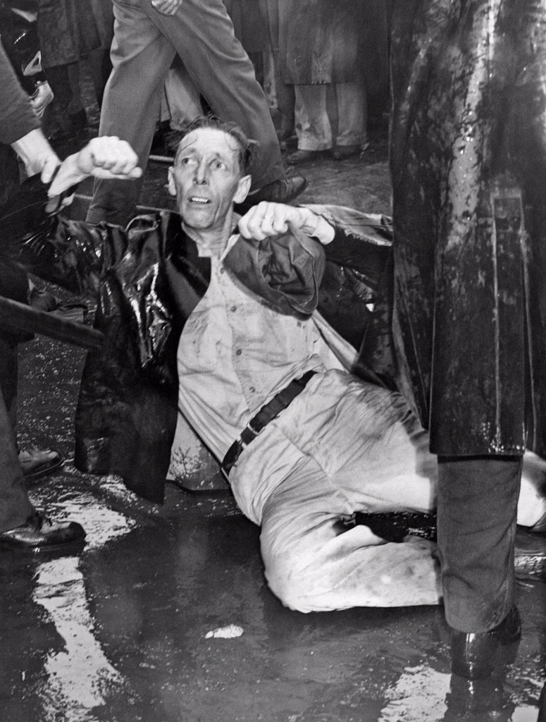 Stock Photo: 1035-12370 Los Angeles, California: October 1, 1946. An injured demonstrator at the MGM Studios lies on the pavement as a police officer holds him.. Many of the paraders are war veterans who have been locked out during the strike.