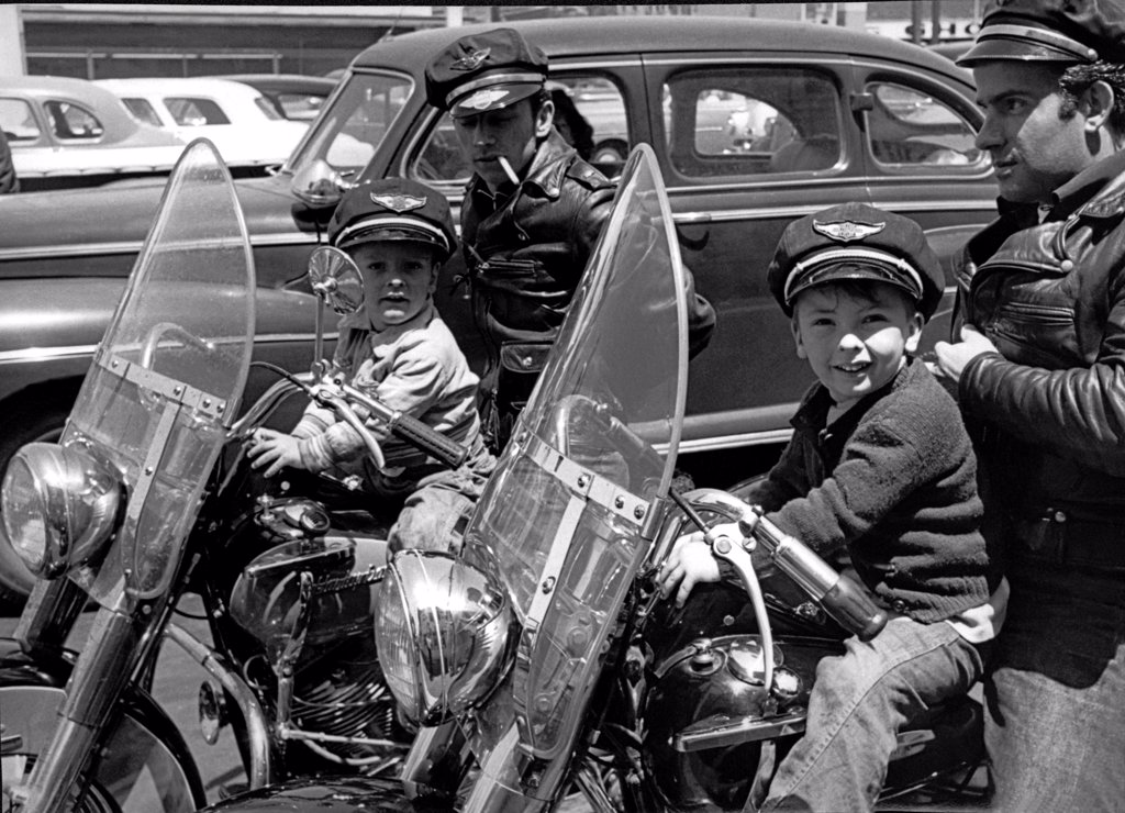 Stock Photo: 1035-12381 San Francisco, California  c. 1954 Two bikers wearing caps and leather jackets on their Harley Davidsons with their small sons in front of them. The boys are wearing caps that say 'Harley Davidson Motor Cycle'.