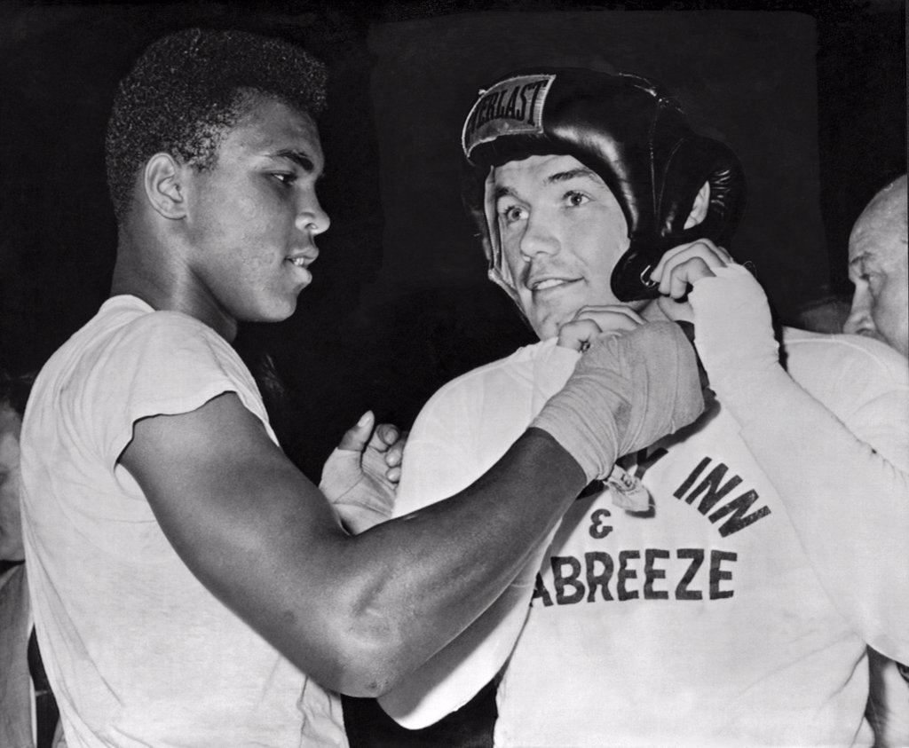 Stock Photo: 1035-12424 Catskills, New York: 1961 Light heavtweight Cassius Clay gives an assist to heavyweight challenger Ingemar Johansson before going a couple of rounds as his sparring partner for Johansson's upcoming title fight with Floyd Patterson.