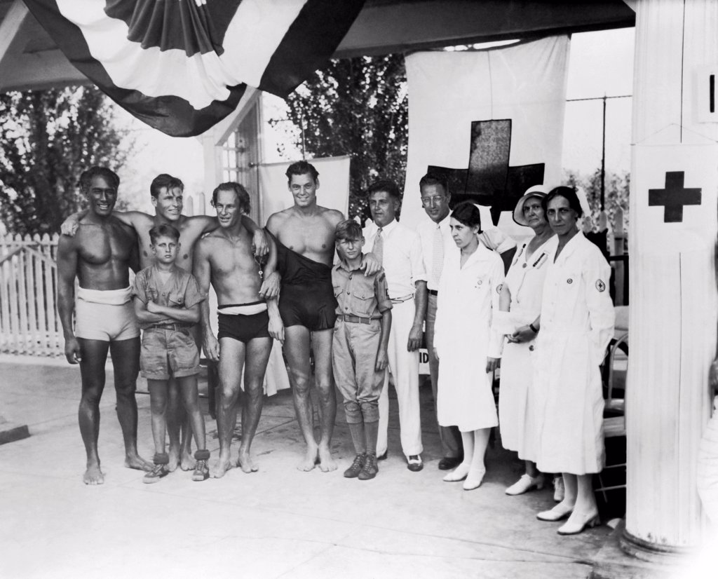 Cincinnati, Ohio:  July, 1932 At the Olympic tryouts are,left to right: Duke F. Kahanamoku, Clarence 'Buster' Crabbe, Harold 'Stubby' Kruger, Johnny Weissmueler, Judge Elmer F. Hunsicker, Paul Goss, Mrs. Mabel Fitzmorris, Mrs. Ella Layne Brown, and Mrs. Carolyn Wayman. Two boy scout messengers stand in front. : Stock Photo