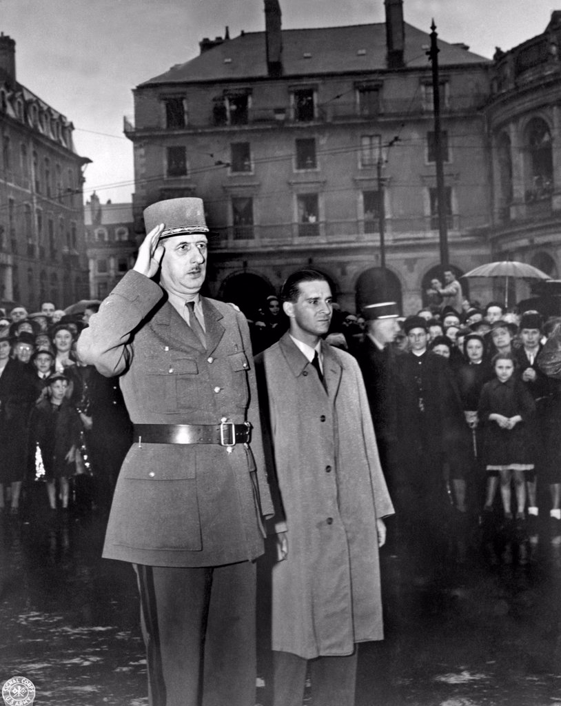 Stock Photo: 1035-12489 Rennes, France:  August 21, 1944. General Charles de Gaulle salutes in the town square of Rennes, France, the capital of Brittany, as the French national anthem is being played. He spoke to a great throng of citizens who stood in a pouring rain to listen to him.