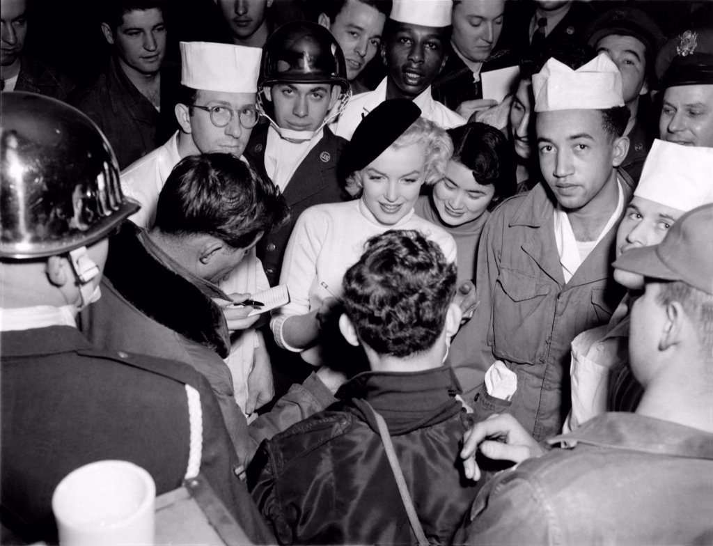 Stock Photo: 1035-12575 Korea:  February, 1954. Marilyn Monroe visits the troops in Korea, entertaining over 100,000 soldiers in 10 different locations. Here she is signing an autograph for a happy soldier.