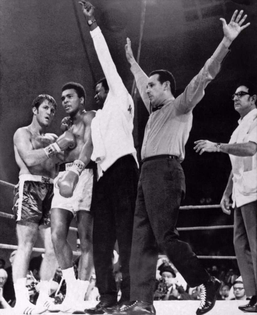 Stock Photo: 1035-12596 Atlanta, Georgia:  October 26, 1970. Referee Tony Perez signals the end of the fight between Muhammad Ali and Jerry Quarry. Angelo Dundee, Ali's manager, is at the right.