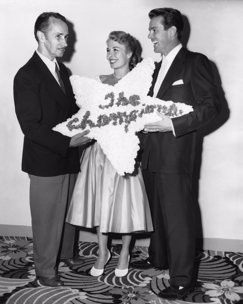 Los Angeles, California:  1952 Noted dance instructer Ernest Belcher presents his daughter, Marge, and son-in-law Gower Champion, with a floral wreath for their performance in the MGM film musical 'Everything I Have Is Yours'. : Stock Photo