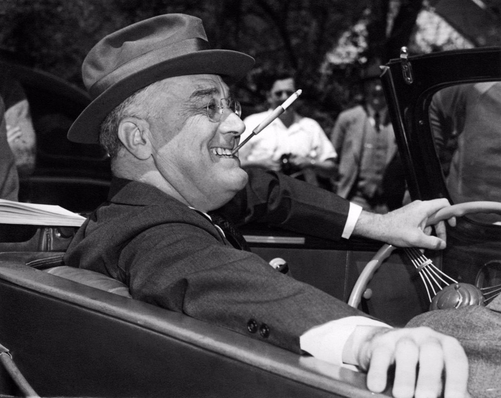 Stock Photo: 1035-12667 Warm Springs, Georgia:  1939. With a cigarette in a holder clenched in his teeth, a smiling Franklin Delano Roosevelt sits jauntily at the wheel of his convertible.