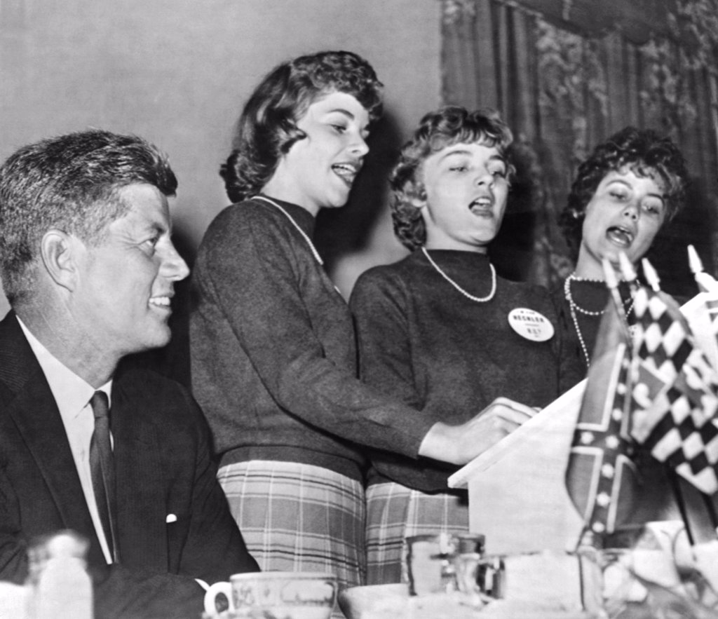 Stock Photo: 1035-12988 Charleston, West Virginia:  September 19, 1960 A smiling Senator John F. Kennedy listens to the Bloomfield sisters sing the West Virginia Democratic campaign song duirng his appearance in Charleston.