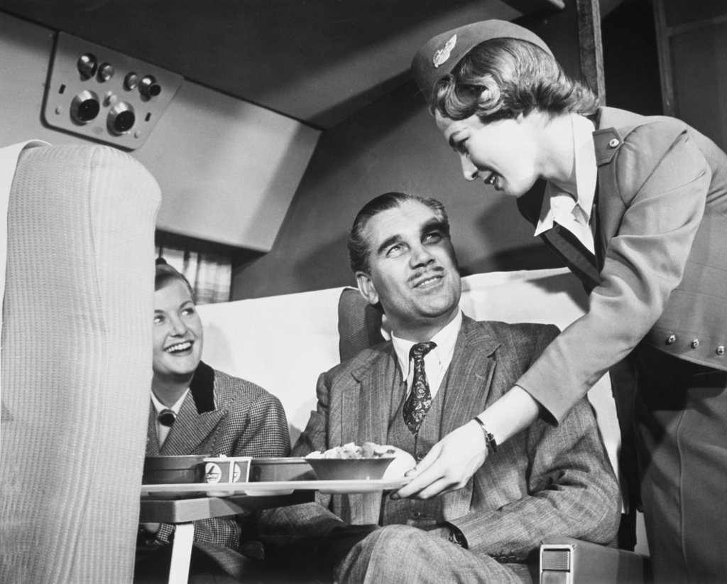 Stock Photo: 1035-180 Airplane stewardess serving meals to passengers in an airplane