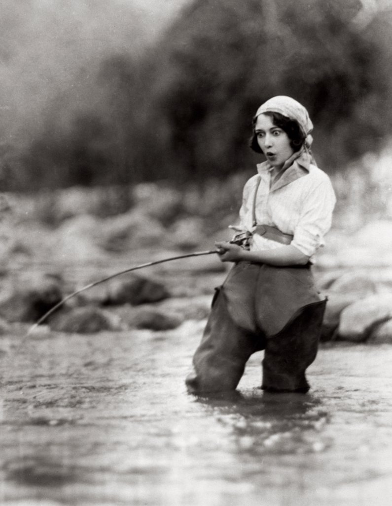 Stock Photo: 1035-220 Young woman fishing in a stream