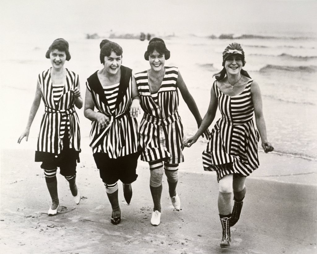 Portrait of four young women running on the beach : Stock Photo