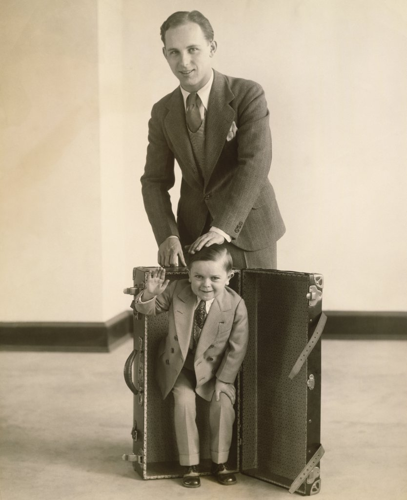 Stock Photo: 1035-385 Portrait of a mid adult man putting the smallest man in a suitcase