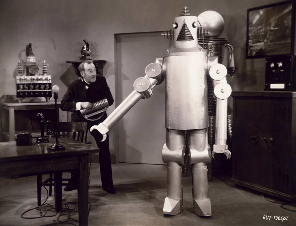 Stock Photo: 1035-454 Senior man standing near a robot
