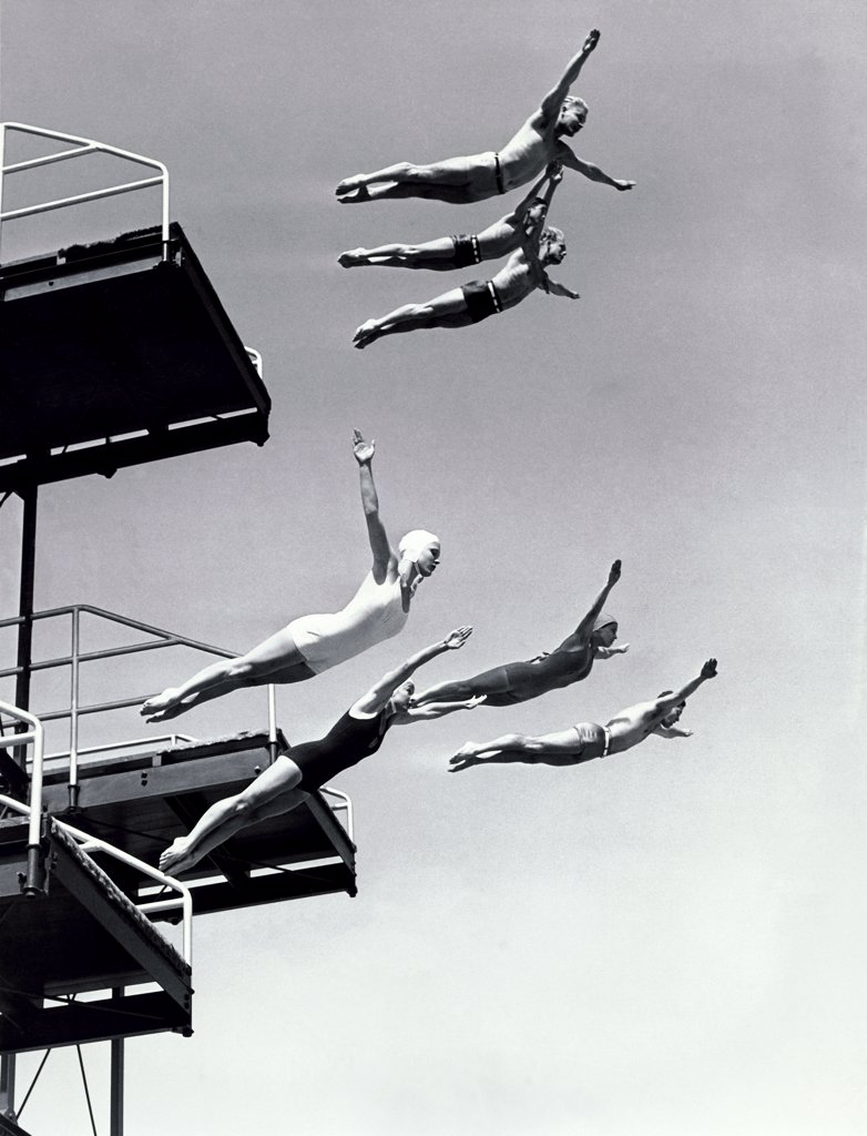Low angle view of a group of people diving from diving boards : Stock Photo