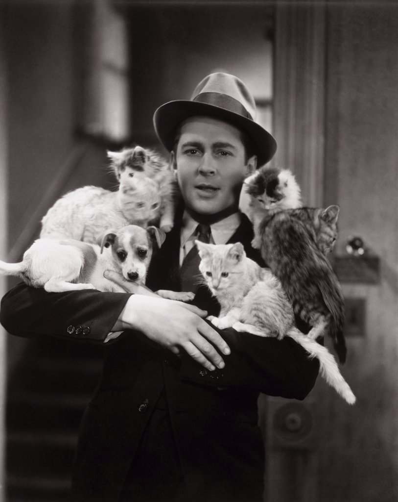 Stock Photo: 1035-611 Portrait of a young man carrying a dog and cats