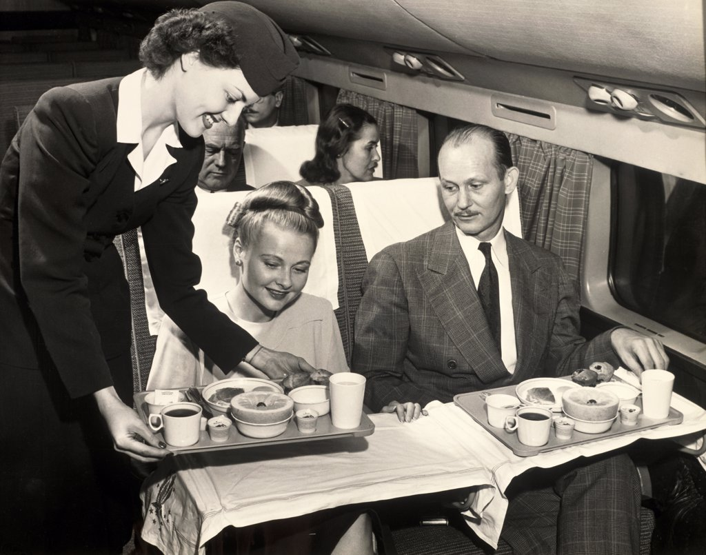 Airplane stewardess serving meals to passengers in an airplane : Stock Photo