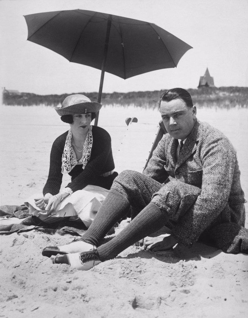 Mid adult couple sitting on a beach, Southampton, New York, USA, 1919 : Stock Photo
