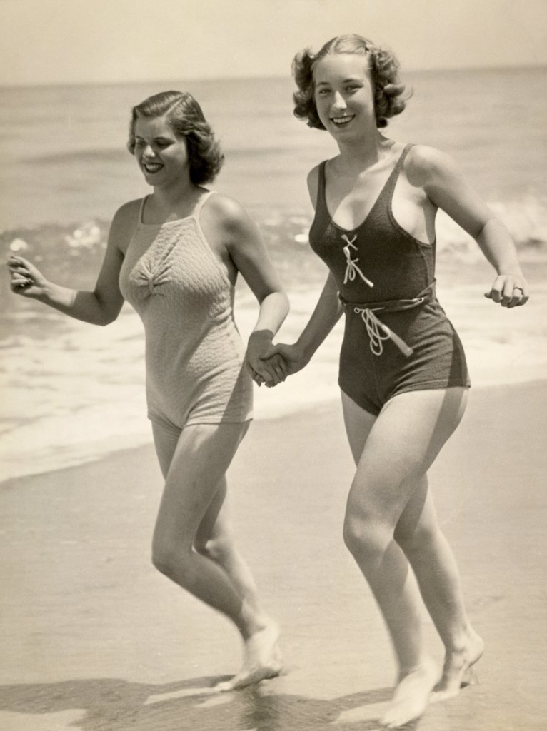 Stock Photo: 1035-665 Two young women running on the beach