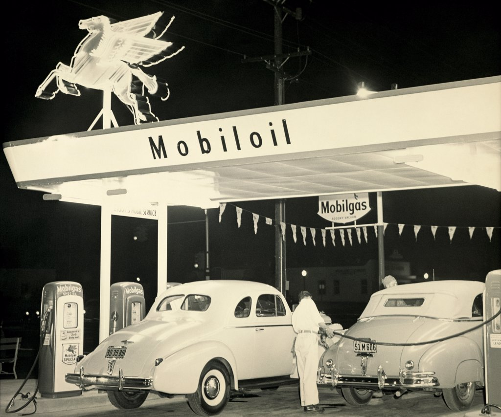 Rear view a of gas station attendant filling a car with fuel : Stock Photo