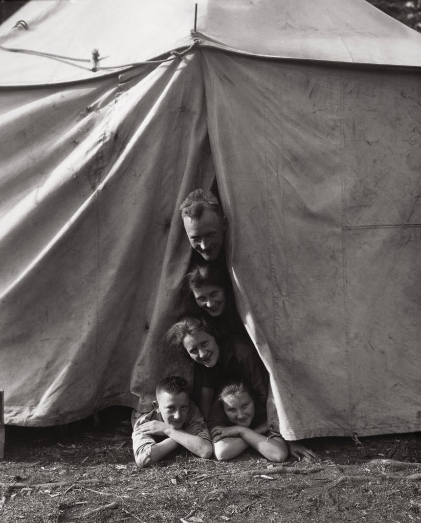 Portrait of parents with their children peeping through a tent : Stock Photo