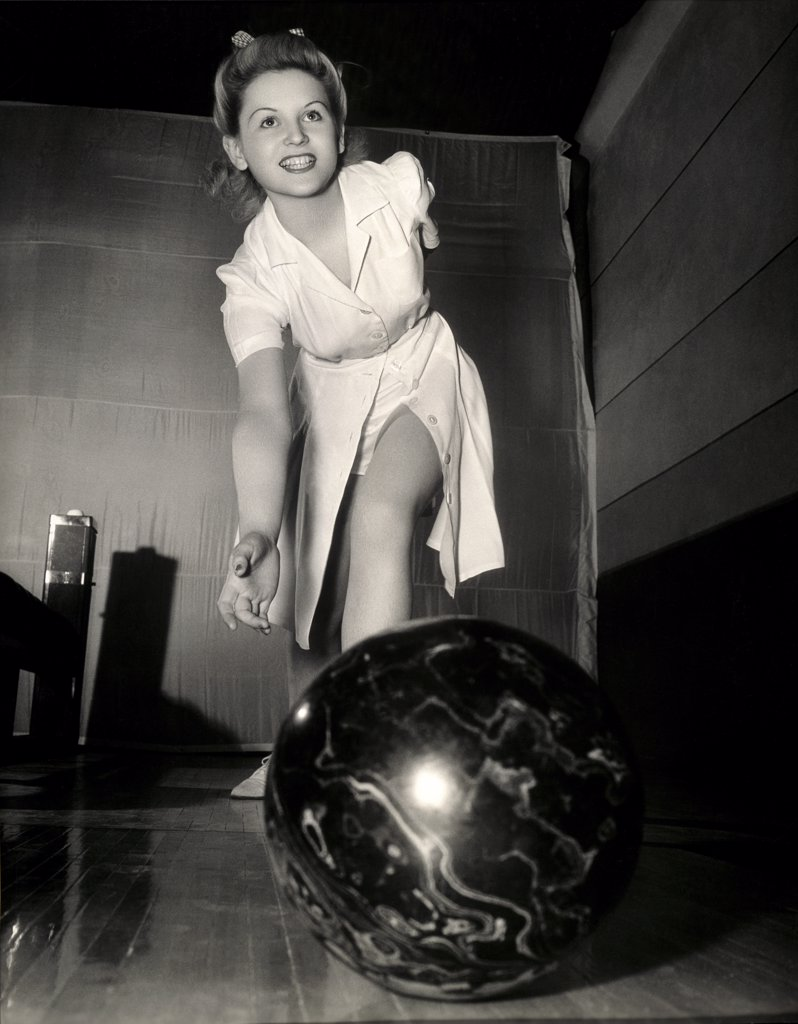 Low angle view of a young woman bowling : Stock Photo
