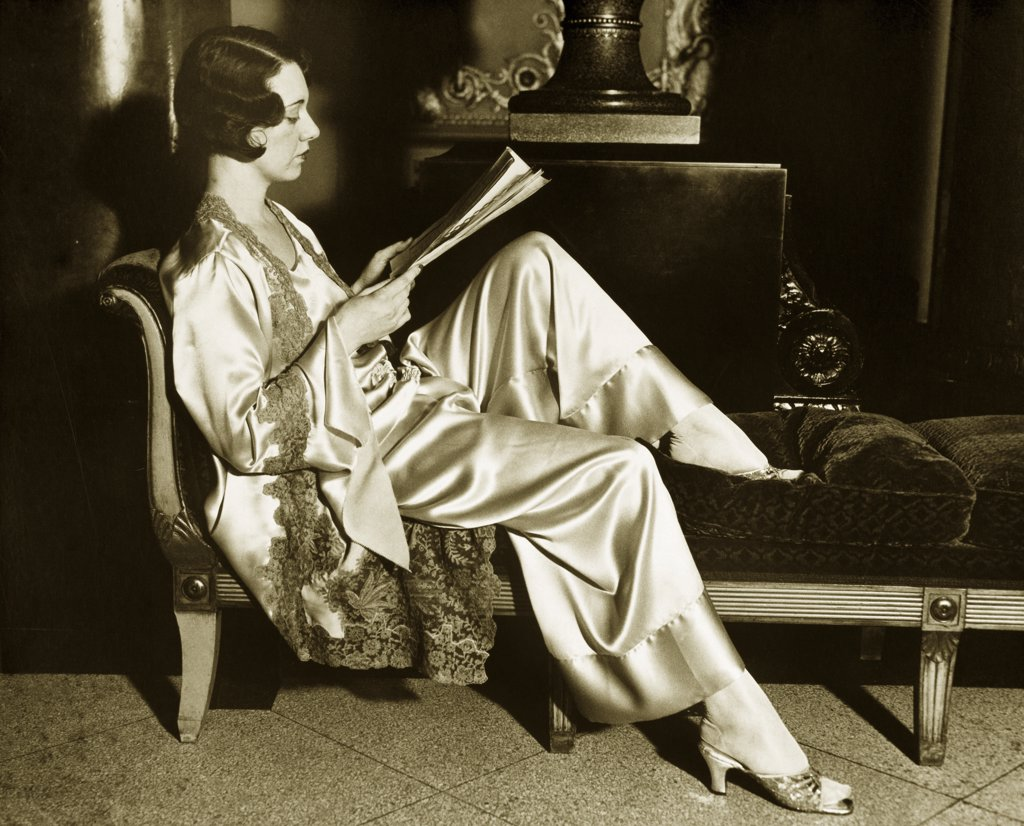 Stock Photo: 1035-861 Side profile of a young woman reading a book on chaise lounge