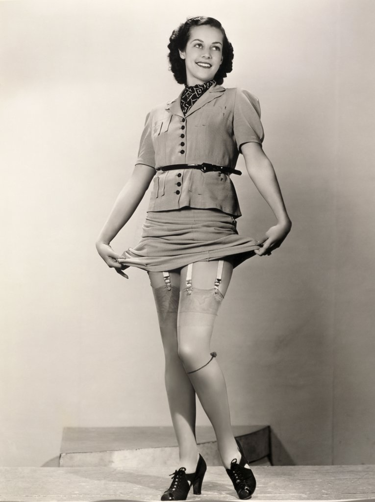 Young woman holding up her dress showing her stockings : Stock Photo