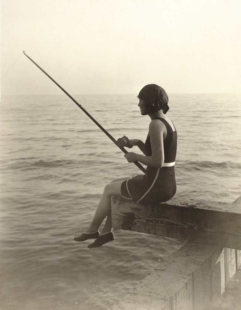 Side profile of a young woman fishing : Stock Photo